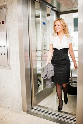 Beautiful blonde woman leaving the elevator.
